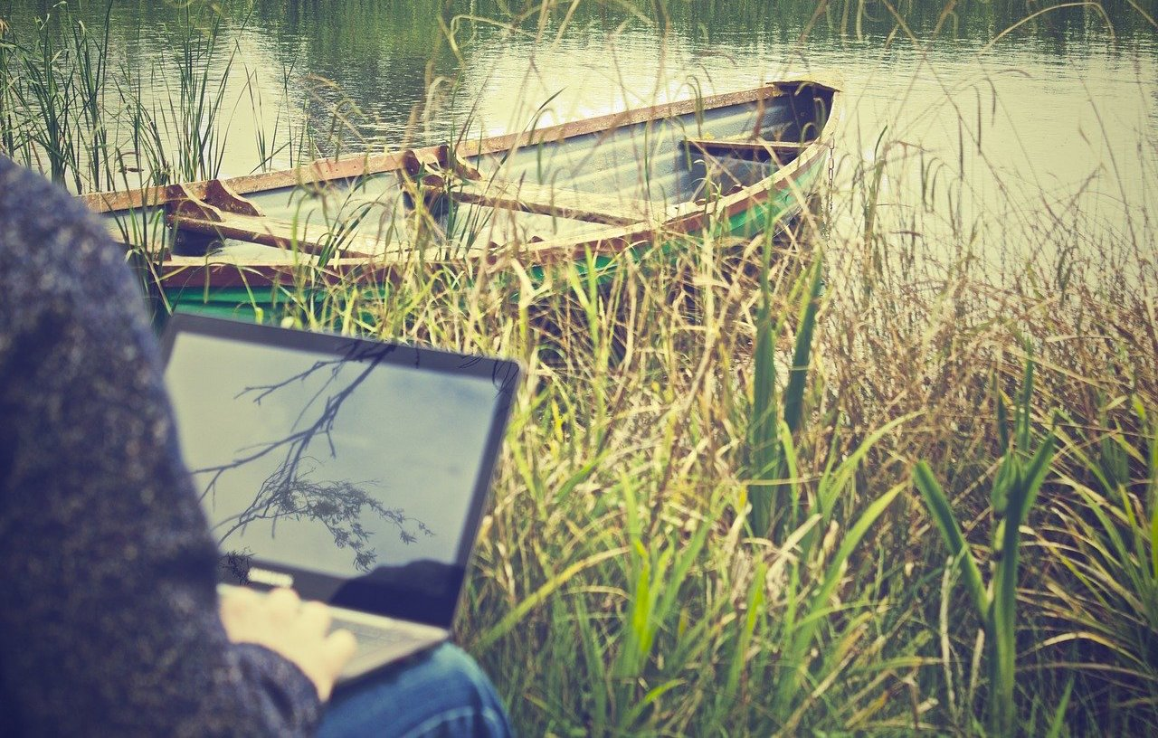 Man with laptop by the river